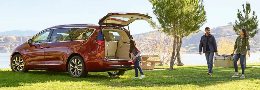 Driver side exterior view of a red 2019 Chrysler Pacifica being loaded by a family after a picnic