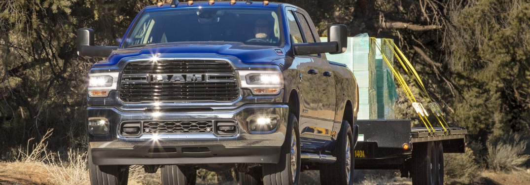 Blue 2019 Ram 2500 Towing a Trailer on a Country Highway