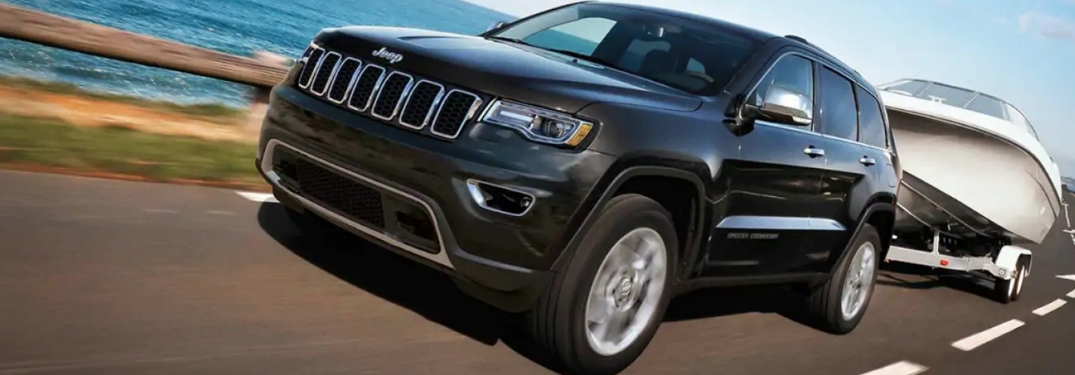 Black 2019 Jeep Grand Cherokee Towing a Boat on a Coast Road