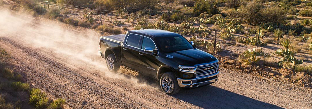 Black 2019 Ram 1500 driving on a dusty road