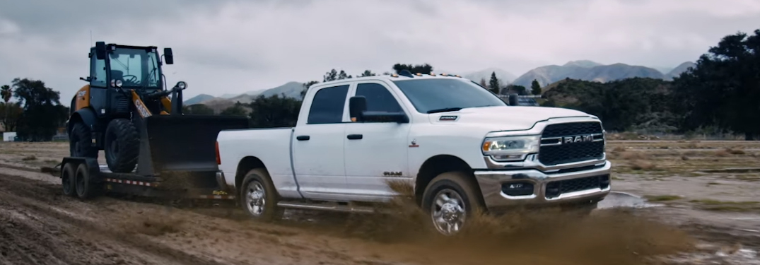 White 2019 Ram 3500 towing a digger