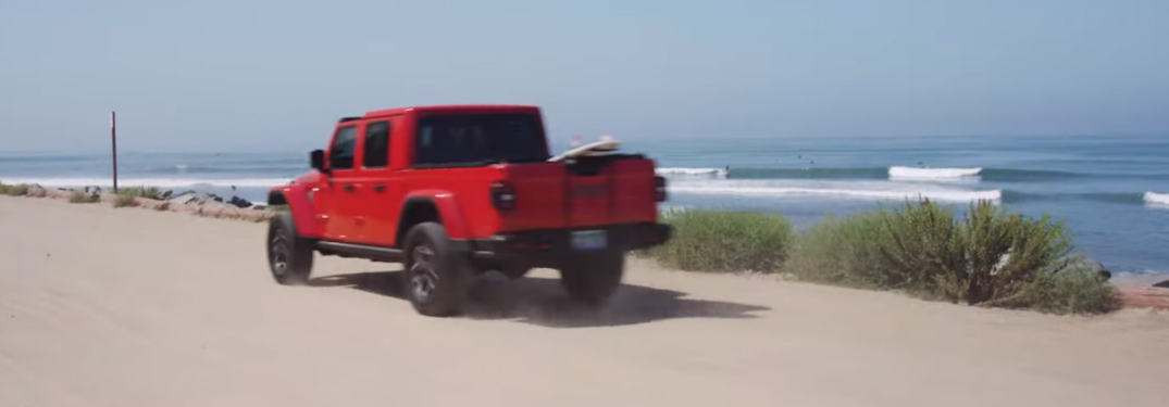 Red Jeep Gladiator driving by the ocean at Huntington Beach