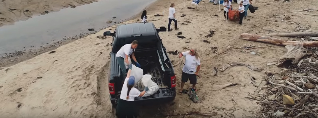 Volunteers for Heal the Ocean loading trash into the pickup bed of a 2019 Ram Heavy Duty