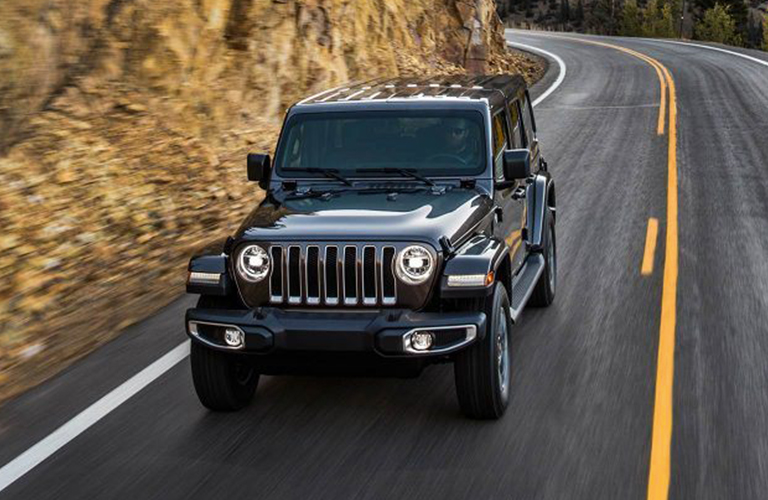 Black 2019 Jeep Wrangler driving on a mountain