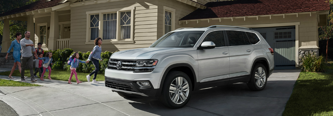 family standing next to 2019 volkswagen atlas
