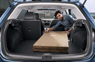 2019 VW Golf exterior looking inside the cargo space with man putting cargo inside
