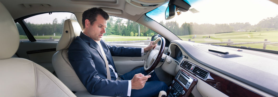 man in luxury vehicle texting while driving