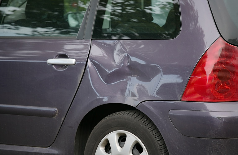 dent in a gray vehicle