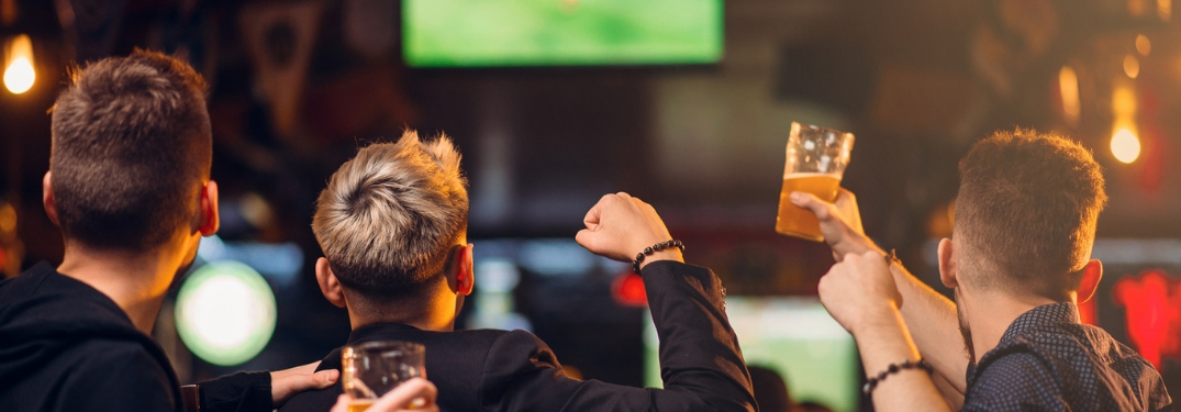 three men watch football in a bar