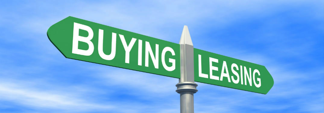 A sign with the word leasing pointed one way and buying pointed the way