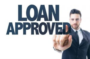 Loan approved text with man standing in the background