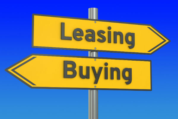 Two signs with the word leasing pointed one way and buying pointed the other way