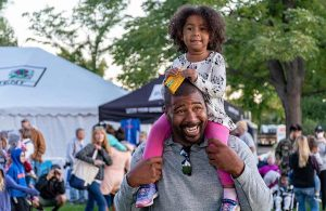 kid on a man's shoulders by a white tent