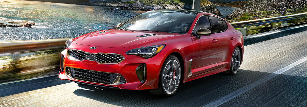 Red 2018 Kia Stinger driving on waterfront road