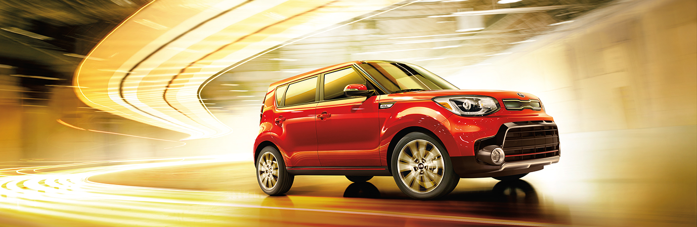 2018 red Kia Soul driving on the road with blurs of yellow lights.