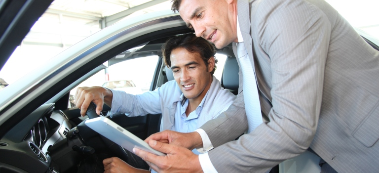 Car salesman helping customer with tablet