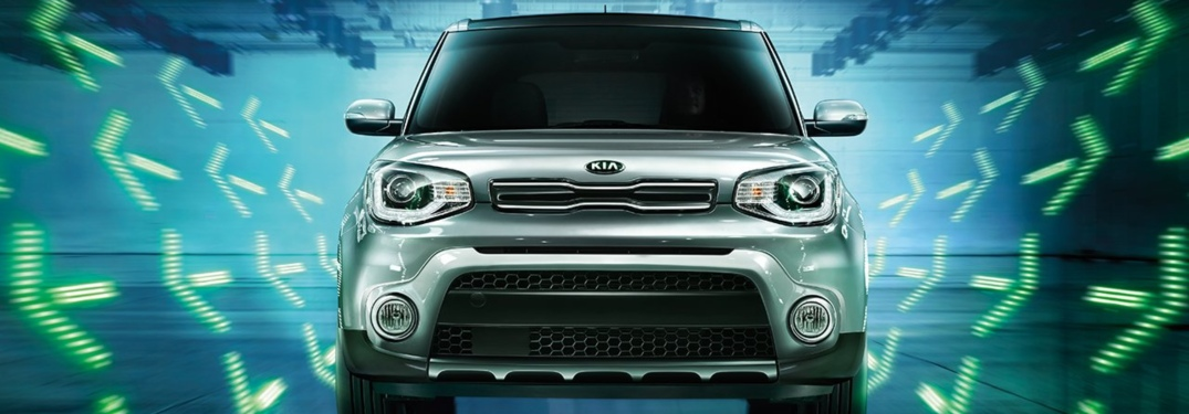 2019 Kia Soul silver front view with a green arrow background
