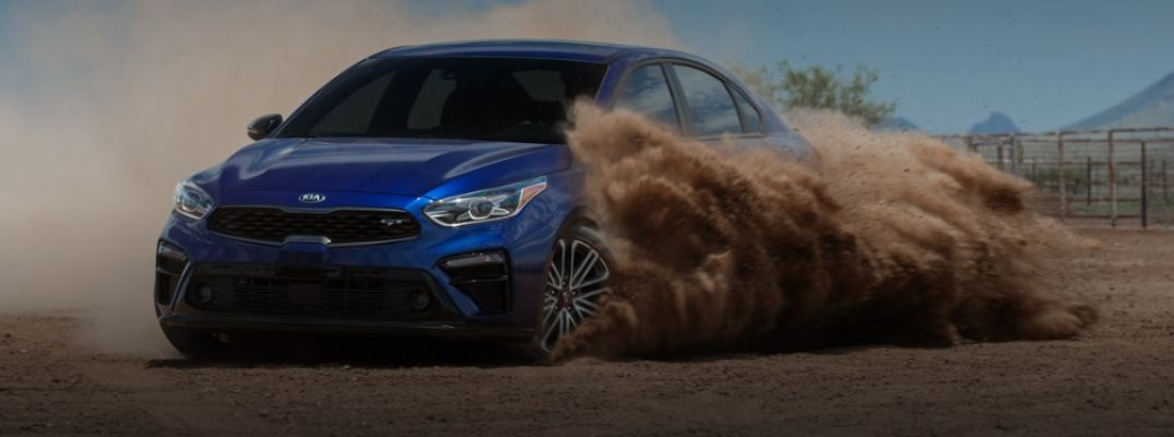 Exterior view of a blue 2020 Kia Forte GT driving through sand