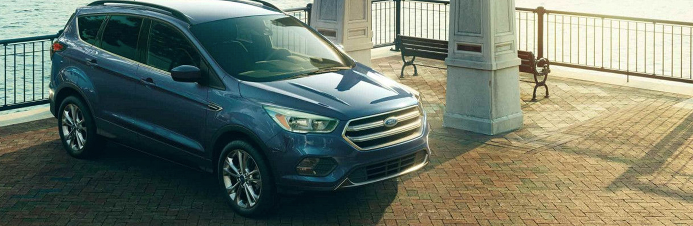 Blue 2018 Ford Escape Parked in front of a fence near the water