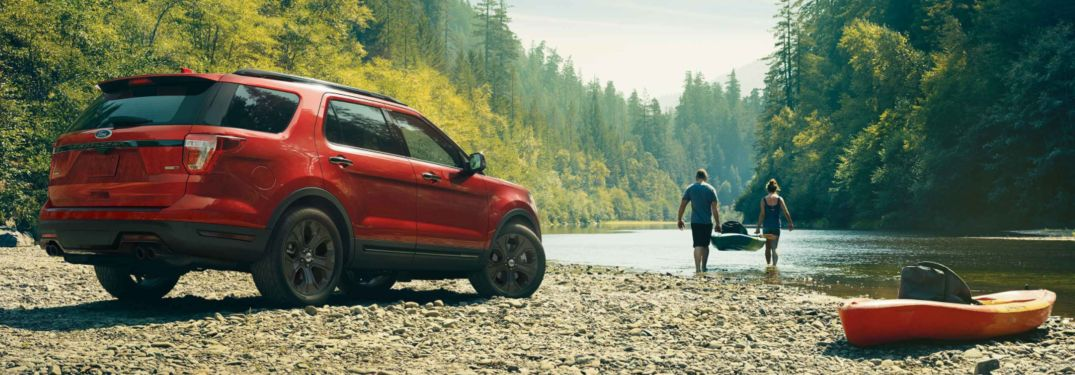 A couple about to start canoeing near a parked 2019 Ford Explorer