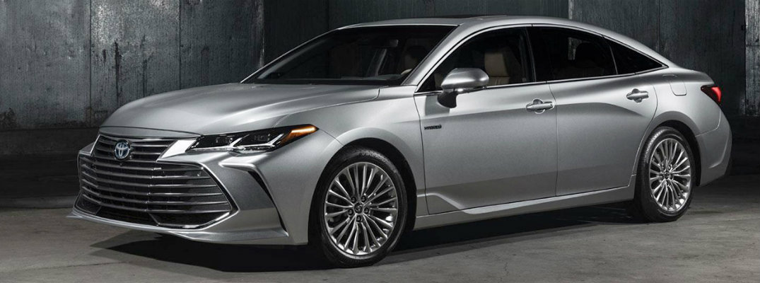 Exterior view of a silver 2019 Toyota Avalon parked in a dimly lit warehouse