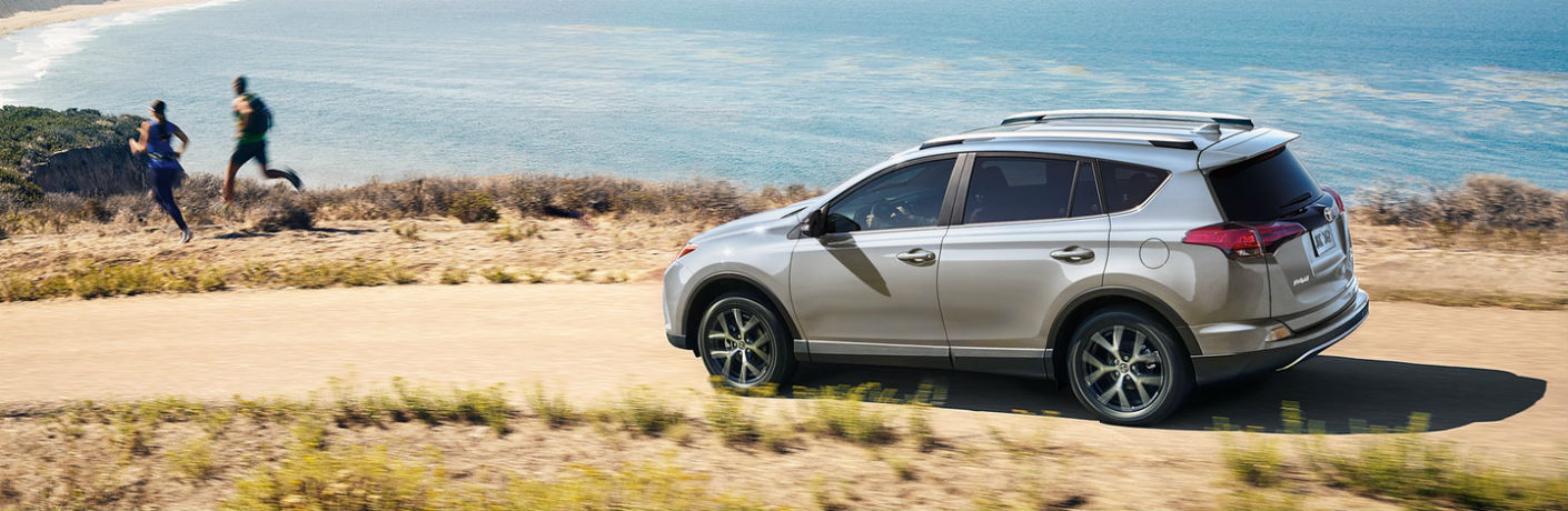 Exterior view of a 2018 Toyota RAV4 parked on a dirt road with ocean in the background
