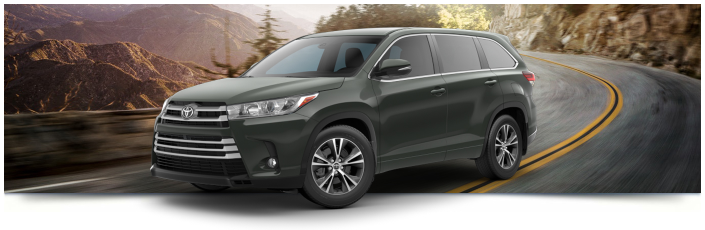 Exterior view of a black 2018 Toyota Highlander against a forest background