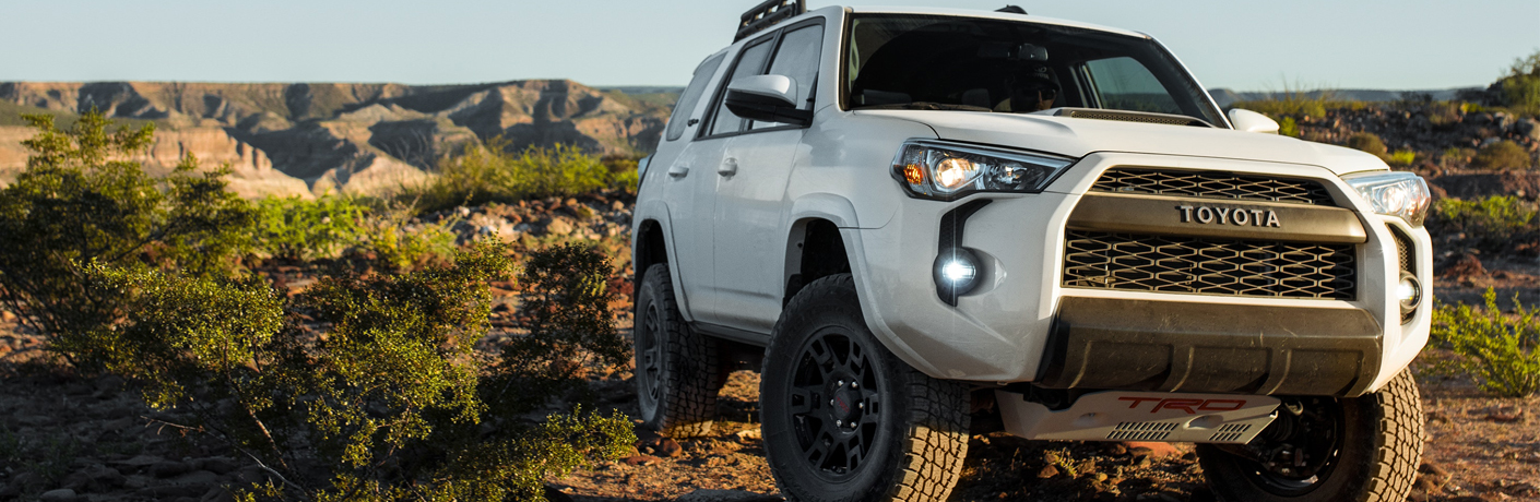 Exterior view of a white 2019 Toyota 4Runner driving over rocky desert terrain