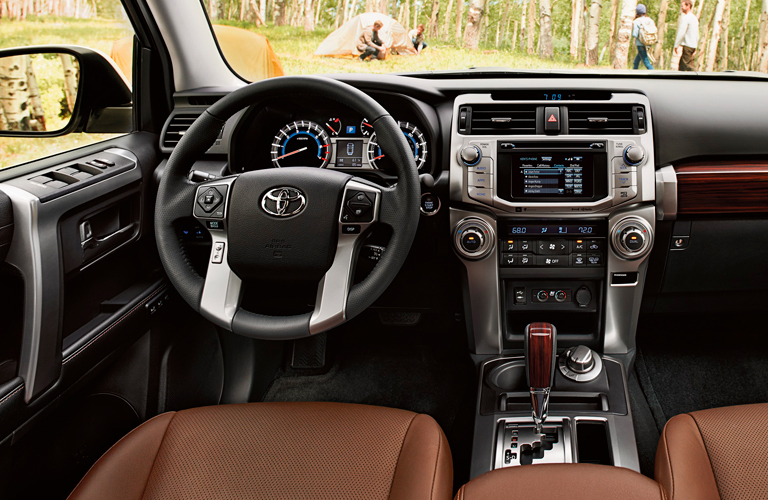 Interior view of the tan front seating and black steering wheel of a 2019 Toyota 4Runner