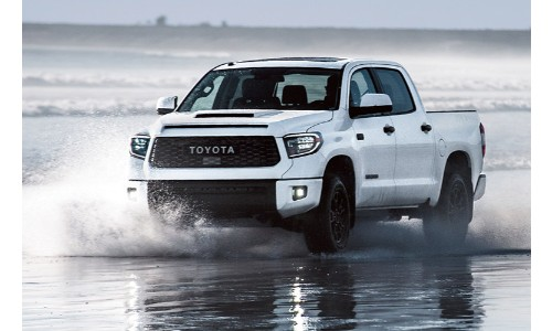 2019 Toyota Tundra exterior shot with white paint color driving and splashing through shallow beach water