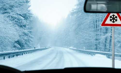 driver's seat view of an icy forest road with a snowflake ice road warning sign