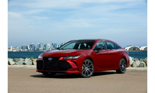 2019 Toyota Avalon exterior shot with red paint color parked on a beach near a wall of rocks and a far away city skyline