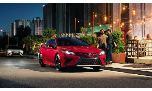 2019 Toyota Camry exterior shot with red paint color parked outside a restaurant at night as two people approach it
