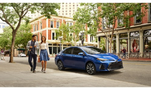 2019 Toyota Corolla exterior shot with blue paint color parked in a city under the sun and tree shade