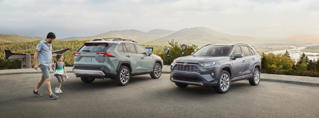 2019 Toyota RAV4 models exterior shot parked outside with forests, rivers, and lakes in the background as a dad and son walk toward the SUVs