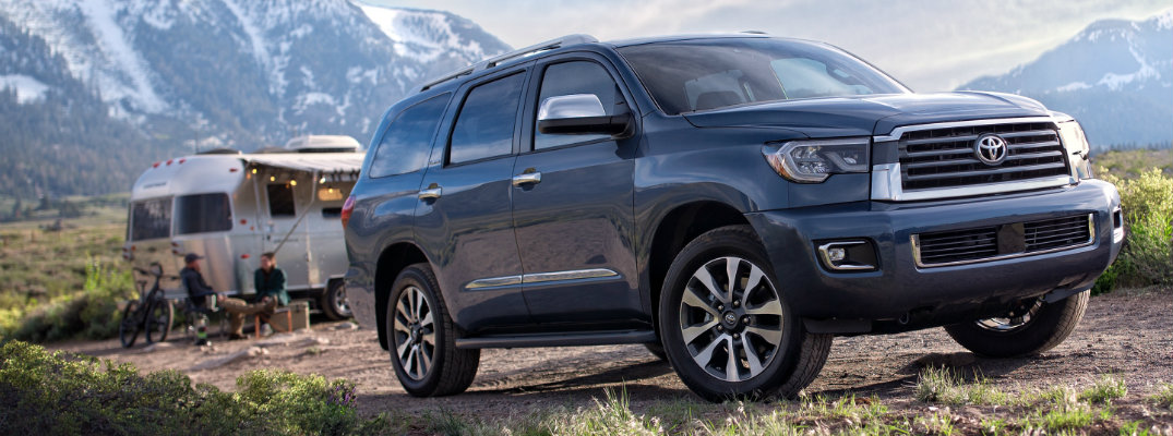 2019 Toyota Sequoia exterior shot with shoreline blue pearl paint color parked in a grassy wilderness near a trailer with a snowy mountain miles away