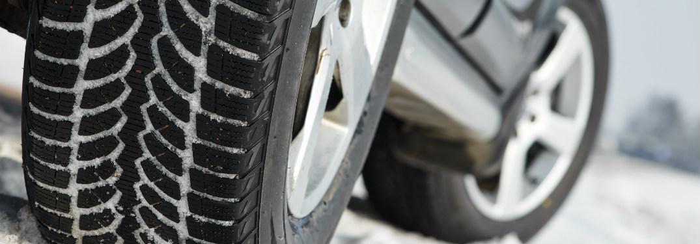 close up of car tires driving through snow