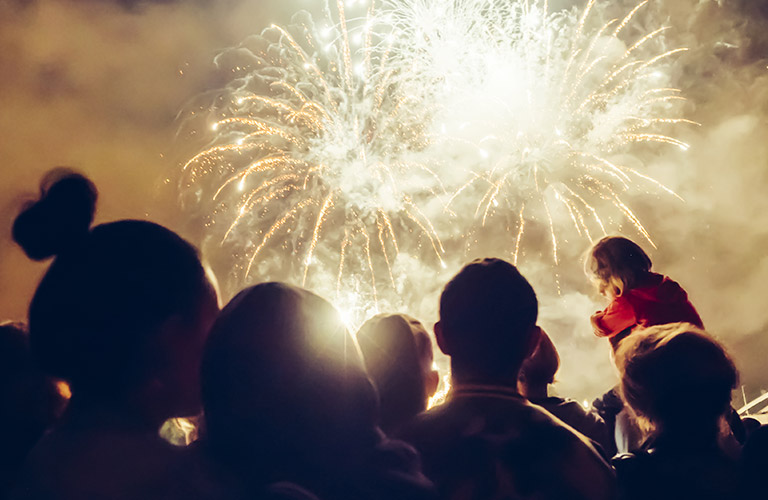 fireworks and people with a golden sky