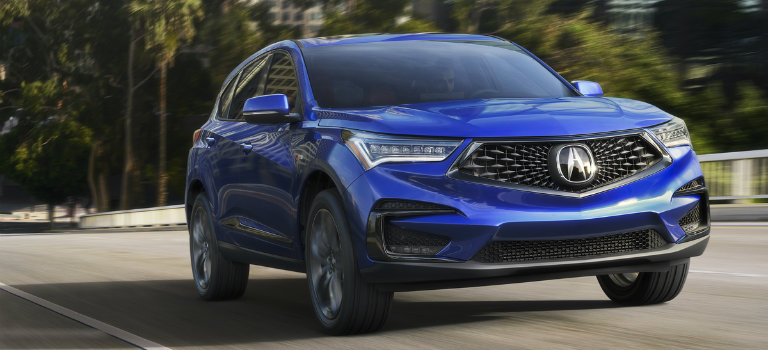Blue 2019 Acura Rdx Driving Along Tree Lined Highway O Acura Of Maui