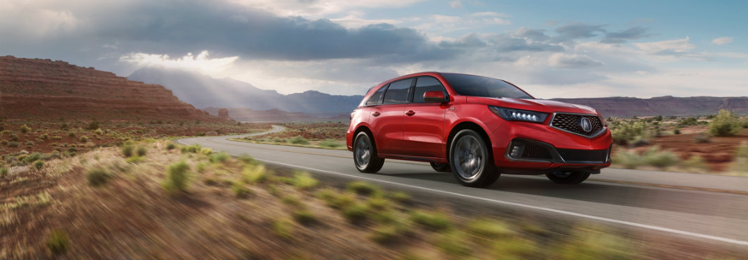 red-2019-Acura-MDX-A-Spec-driving-along-country-highway
