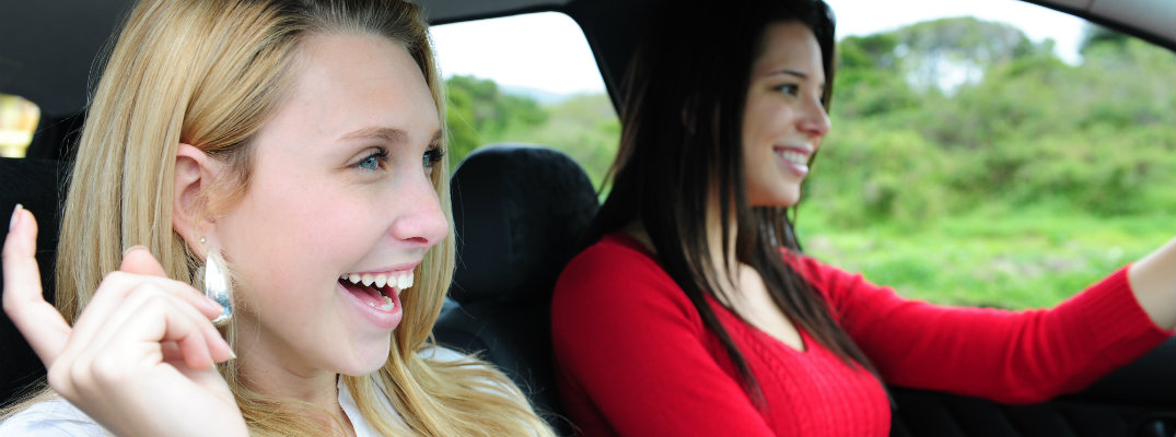 Two women listening to a podcast in a car