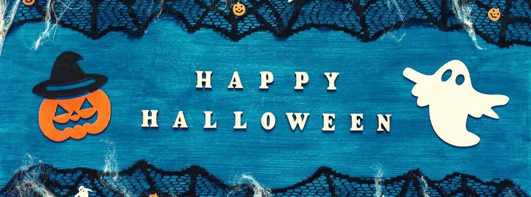 Happy Halloween banner with white block font against a blue background with black cobwebs