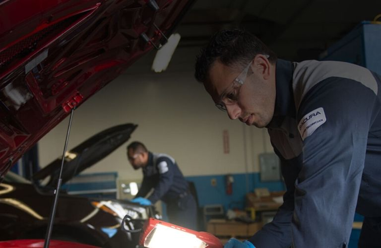 Image of an Acura service technician working under the hood of an Acura vehicle