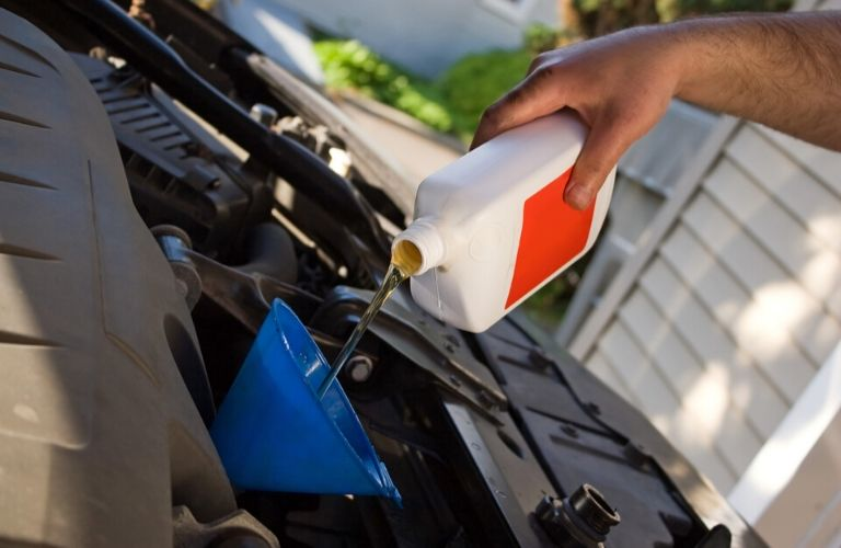 Image of an individual changing the oil in a vehicle