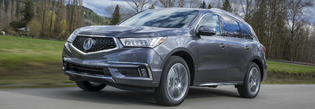 Grey 2020 Acura MDX driving by a grassy field