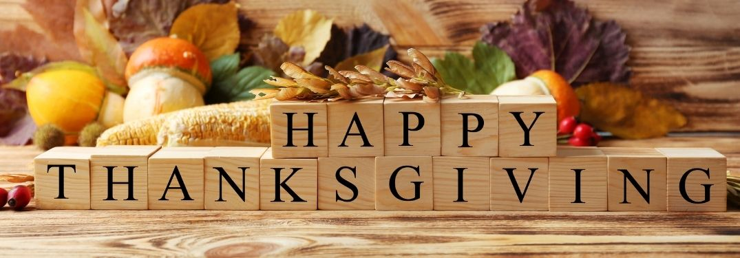 Blocks Spelling Happy Thanksgiving with Fall Decor in Background