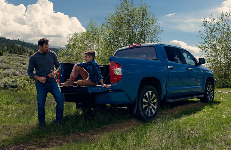 A blue-colored 2021 Toyota Tundra with a dad and son standing and sitting near the rear