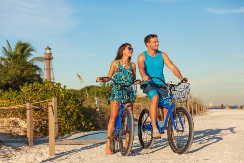 A man and a woman each on a bike while on a beach