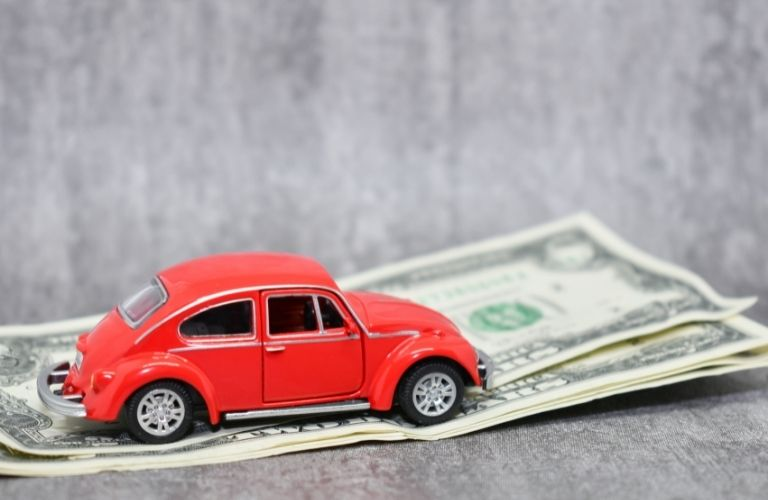 small red car over some dollar bills