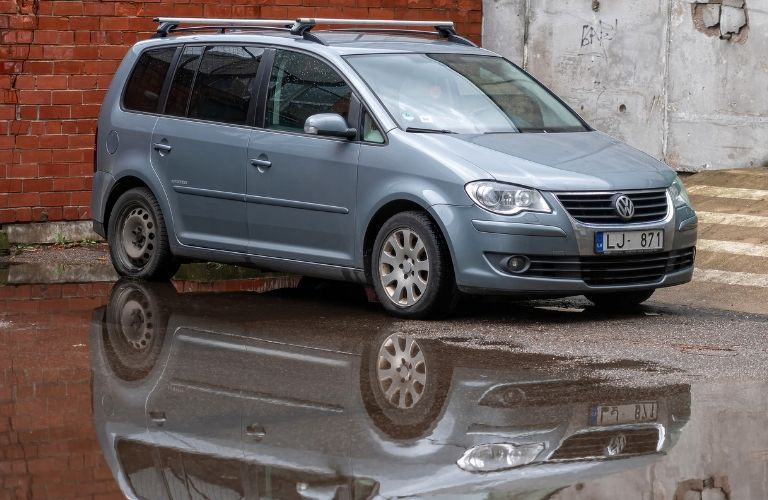 a blue minivan parked and its reflection seen over the water